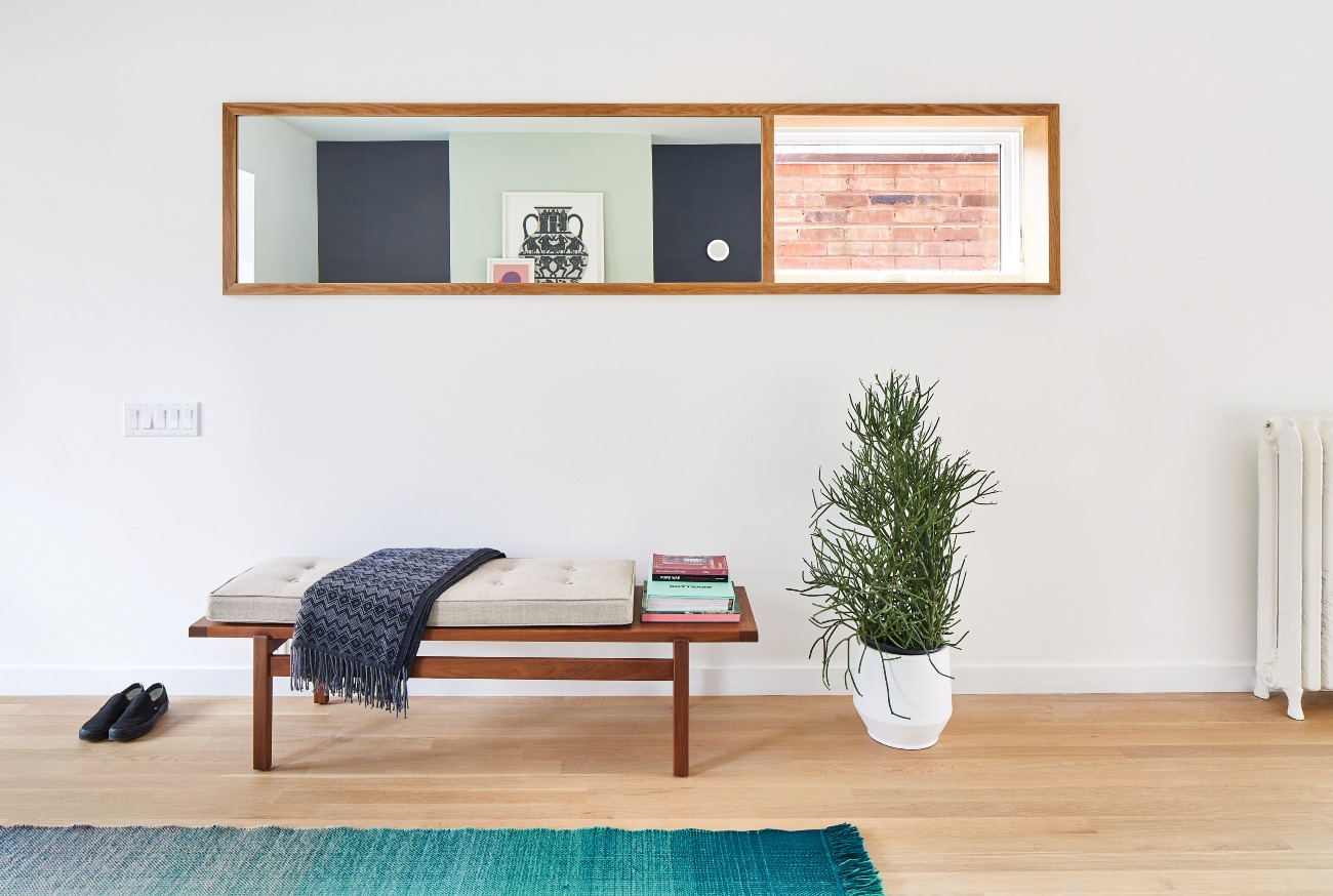 White oak is the star here, trimming the window–mirror hybrid and running across the floors (by Graf Brothers). Bench from DWR; rug from Quasi Modo.