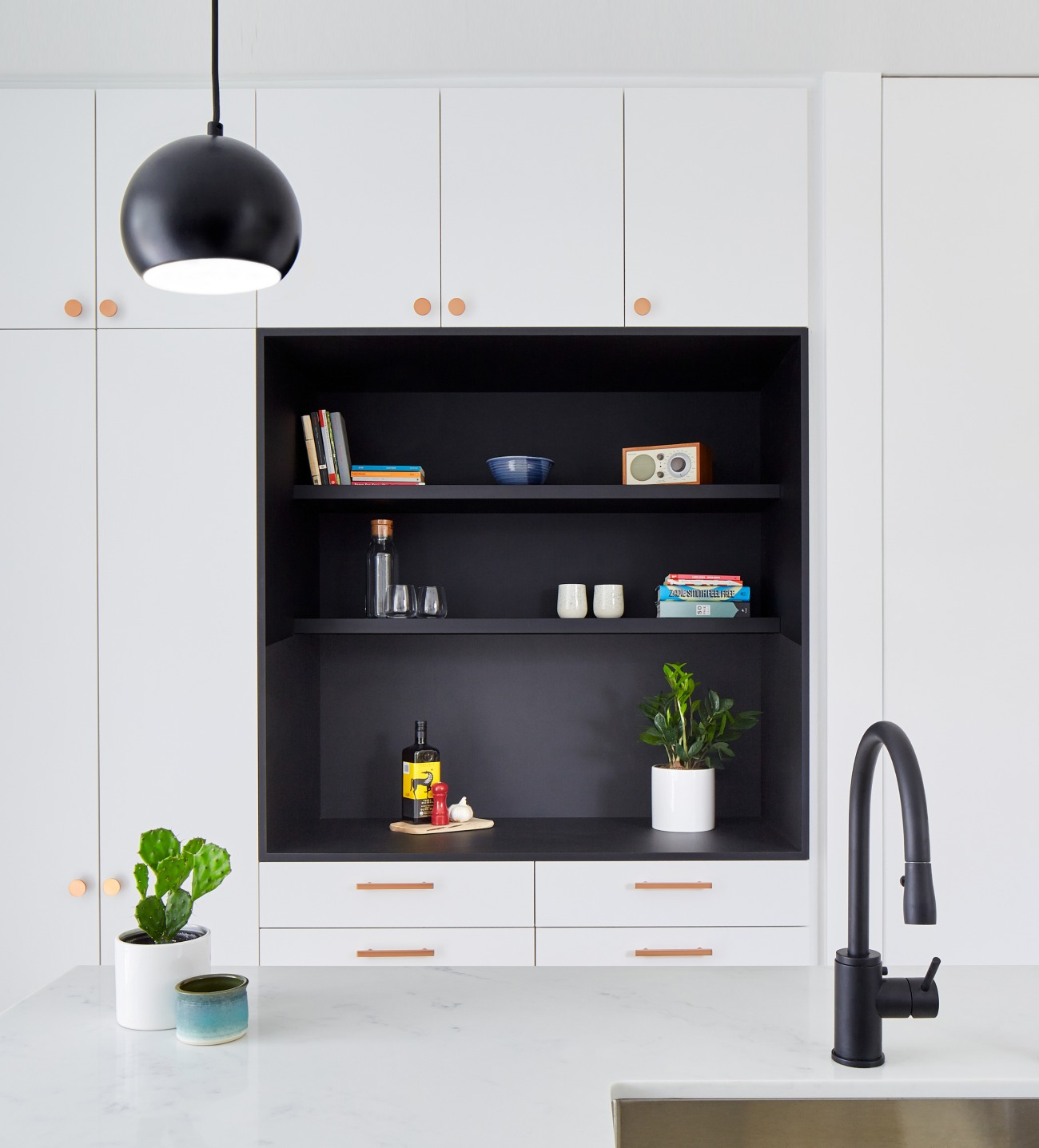 Copper finishes warm the high-contrast kitchen. Pendants from EQ3; hardware from Schoolhouse Electric and CB2; Rubinet faucet.