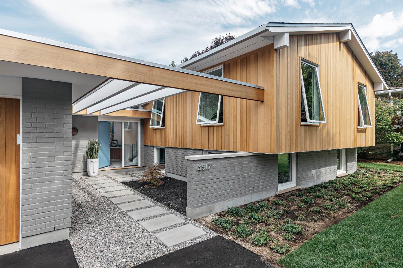 What looks to be original postwar exterior styling is mostly new. The studio replaced a well-set-back garage, and a new garage – now flush with the home – was added, as were the glulam beams. New brick here matches the old; elsewhere, the home was treated to shiplap cedar siding.
