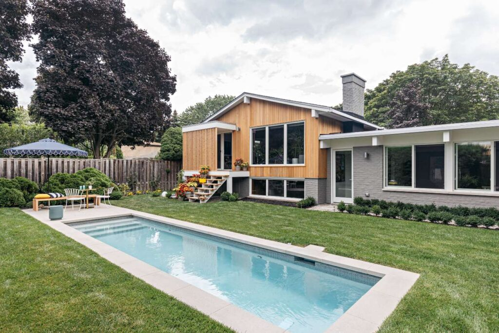 In the backyard – with grounds by Couture Landscapes and lap pool from Gib-San Pools – one can see how the original gabled portion of the house meshes with the lower, renovated section thanks to impeccable brick and siding.