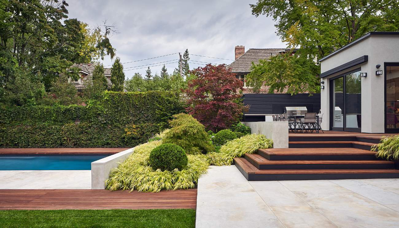 An extended sequence of wide platforms by Amantea Architects clarifies the shift from ipê dining terrace to limestone patio to lawn and pool below. Plantings by Tina McMullen.
