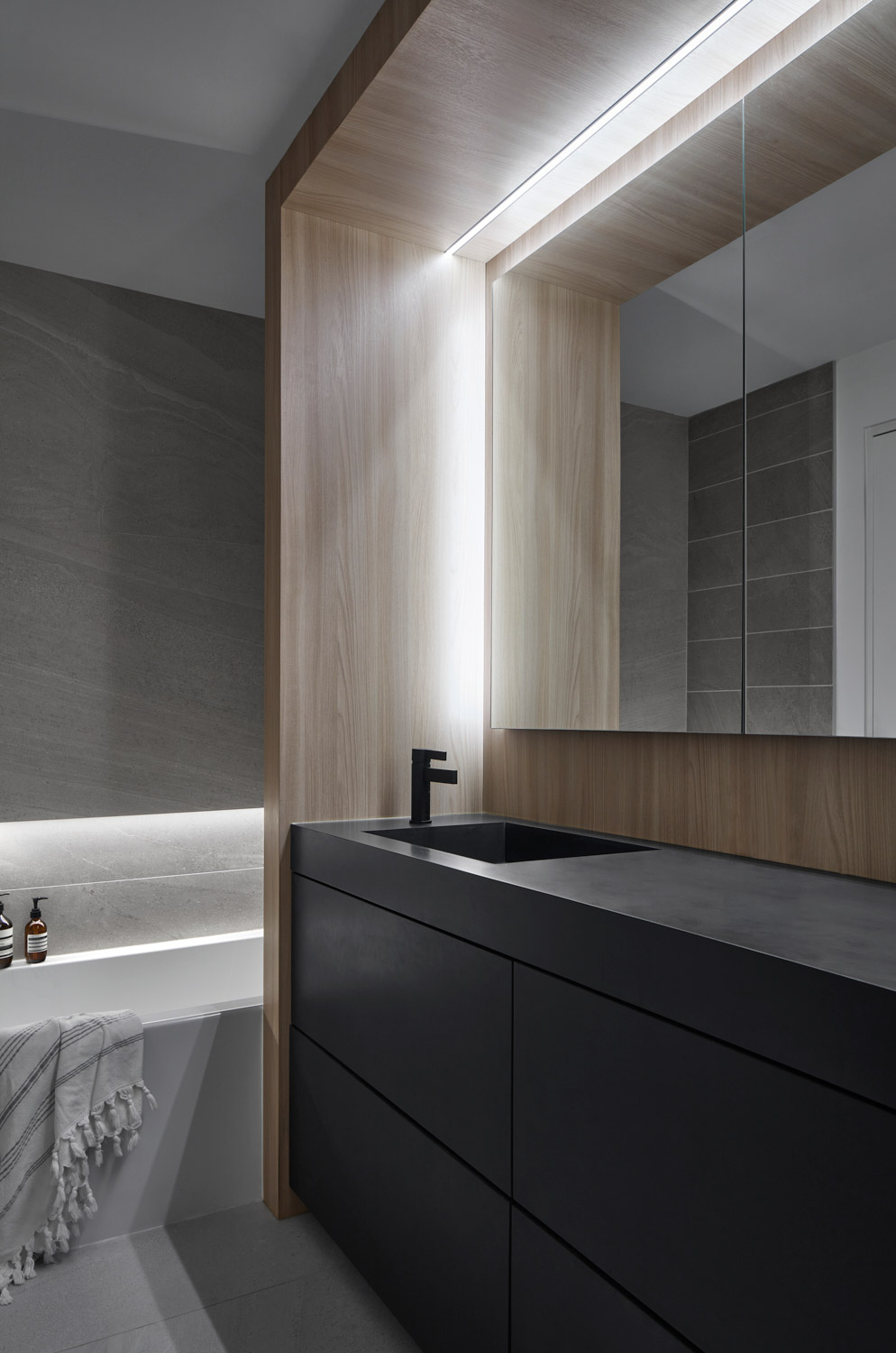 Strip lights are used throughout the home, including here, in the bathroom, where it's recessed into the wall. The vanity is clad in Corian; fixtures by Lusso Stone.