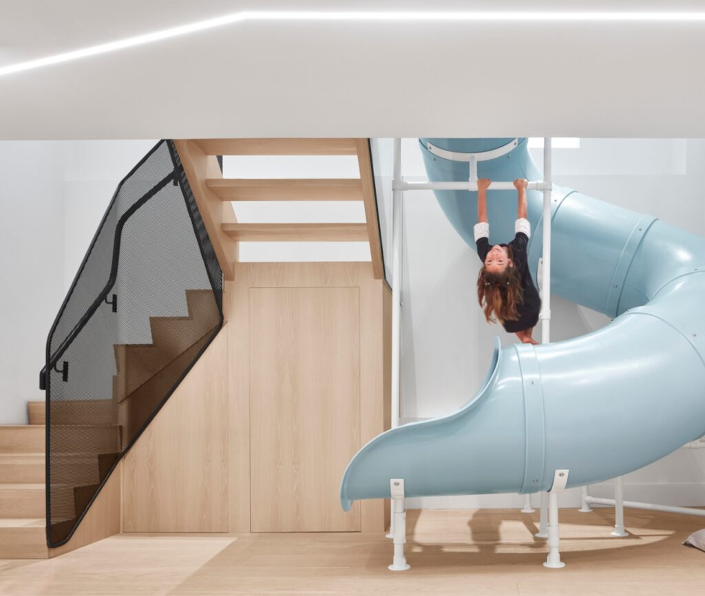 The slide, sourced from SPI Plastics, provides an alternative avenue to go downstairs (and for the kids, to go up). The screen around the stairs is powder-coated steel, while the storage space was stained to match the flooring.