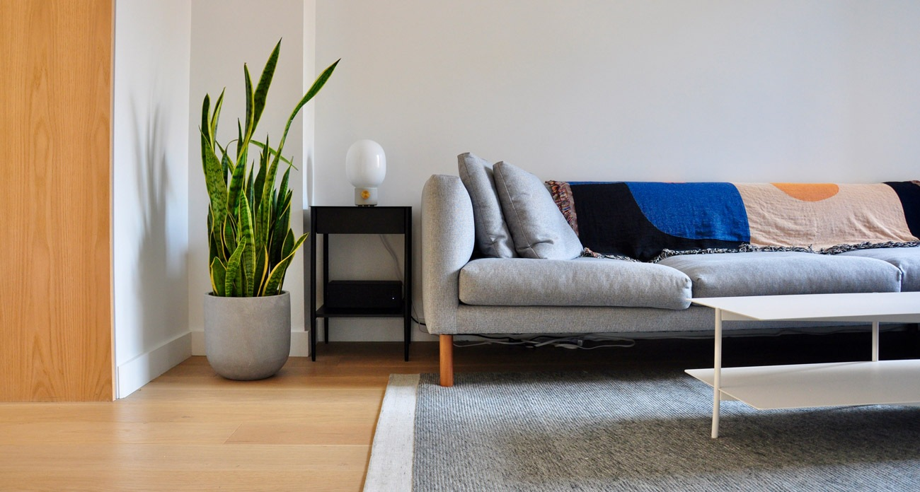 The sectional, from EQ3, is flanked by Gron + White's JWDA lamp and an Umbra table.