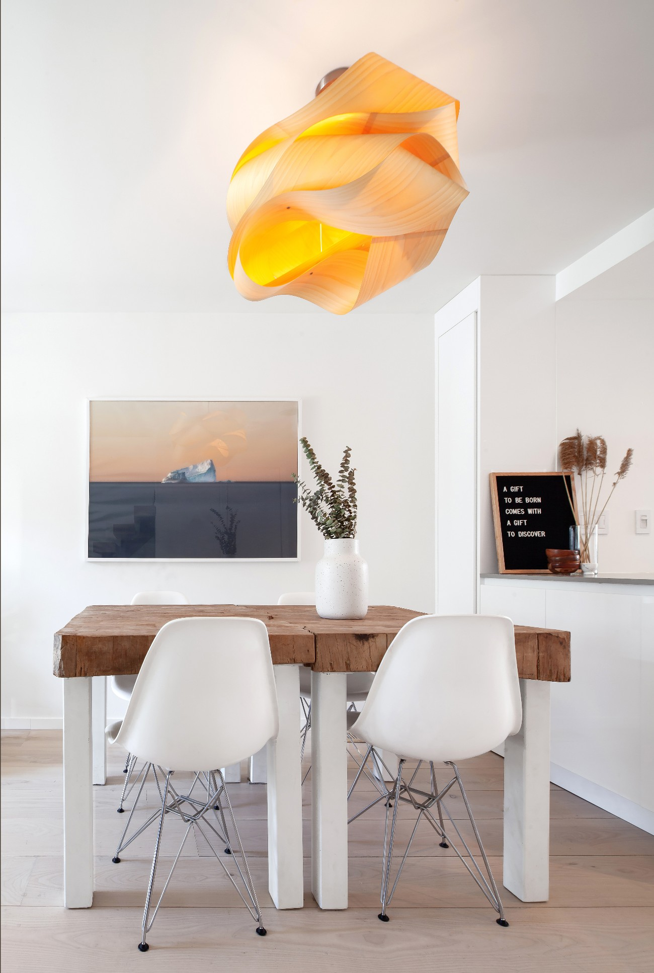 Below the LZF ceiling lamp, the paired dining tables were cut from a salvaged butcher's block. The photograph behind is by Canadian landscape photographer Curtis Jones.