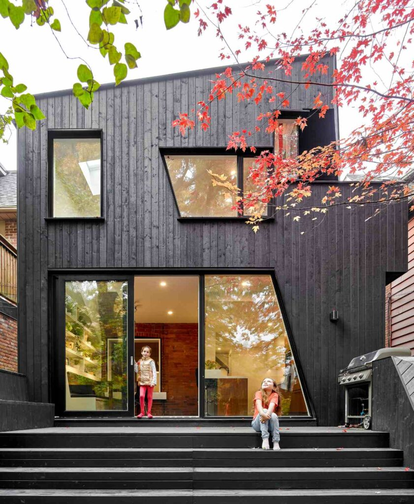 The non-traditional geometry plays off of the Edwardian's gabled roof. The painted black wood cladding is supplied by Cape Cod Finished Wood Siding, while  pressure treated wood was used for the deck and stained black to match.