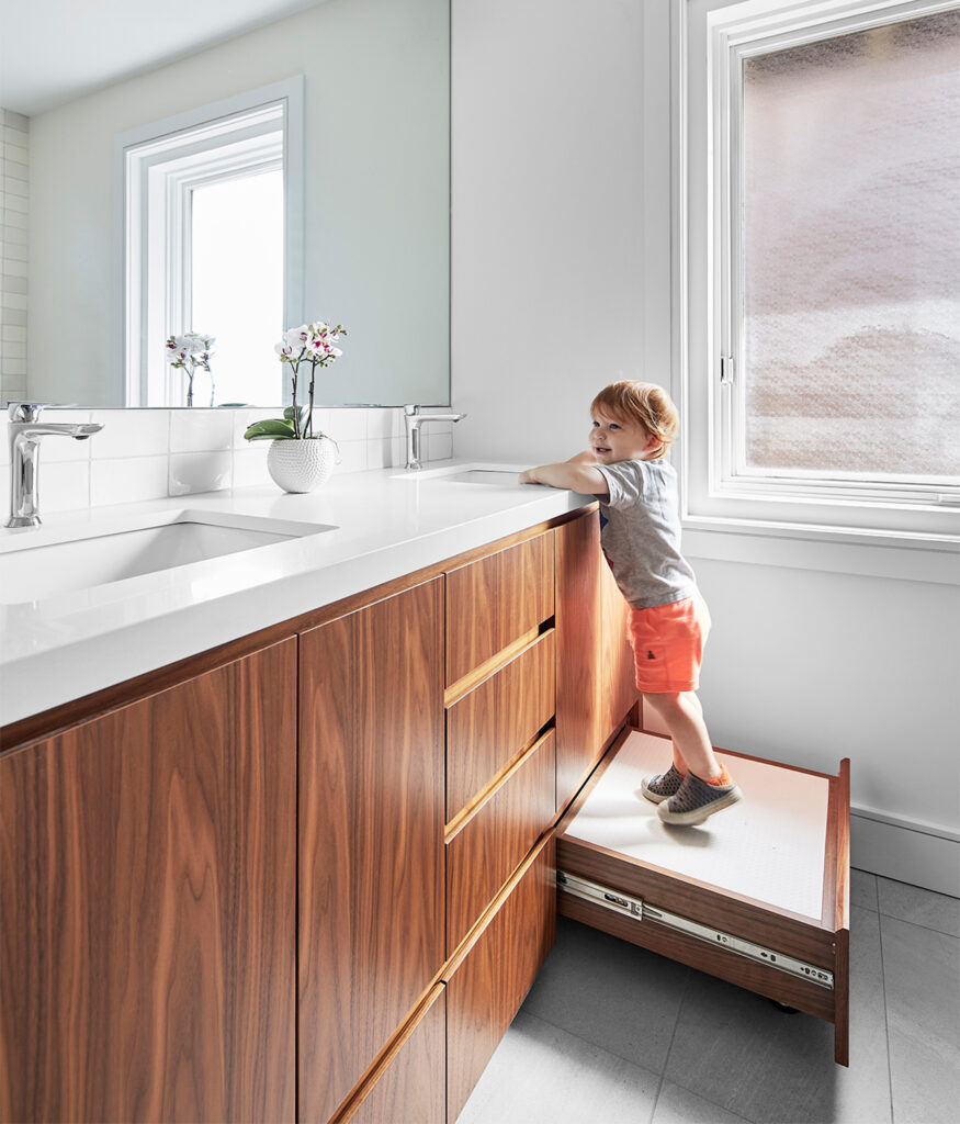Because the homeowners are frequently visited by the grandkids, Myers updated a family bathroom, complete with stowable step stool. Walnut cabinetry and custom vanity by Millworx; Artemide sconces.