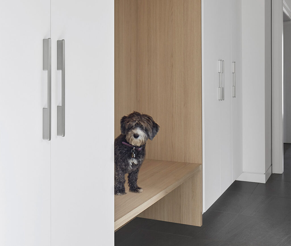 Marley peeks out from the storage system in the new mudroom. The cubby is clad with water-resistant Decotec; flooring from Stone Tile.