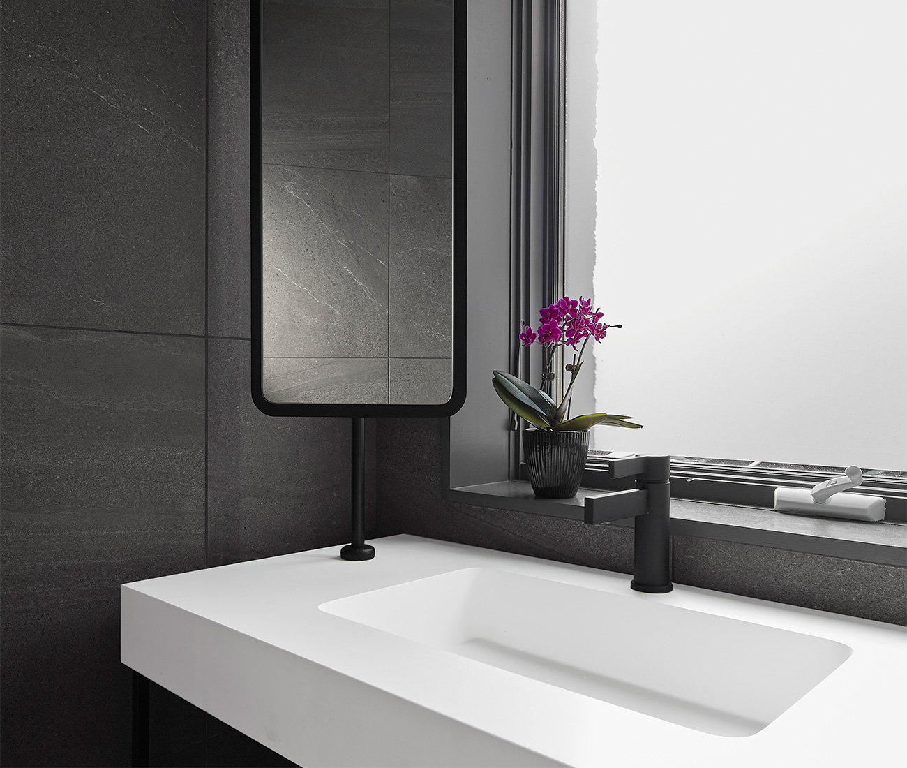 Preferring not to block this powder room's single window, Myers opted for a pivotable mirror (by Homa Signs) instead. Faucet and vanity from Roman Bath.