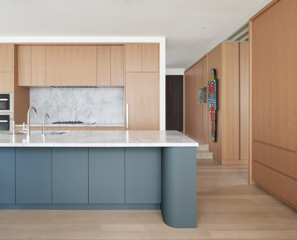 Bassani Fine Cabinetry clad the sculpted casework of the kitchen island in Fenix surfacing, a material with a matte finish and soft feel.