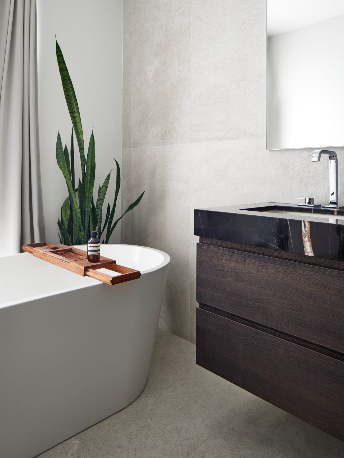 The freestanding tub is by Maax, while the vanity, by Scavolini, is topped with Nero Tunisi marble from Olympia Tile + Stone. Fixtures by Grohe; floor and wall tiles from Stone Tile.
