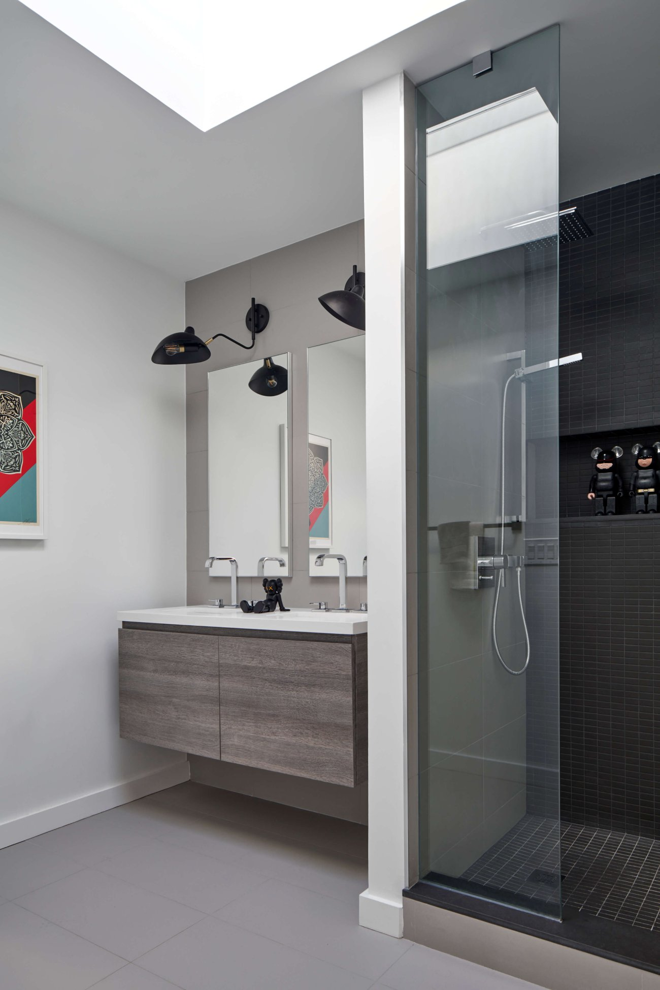 Robocop and Batman Bearbrick figures stand sentinel in shower niche.The vanity, by Scavolini, is topped with pure white Caesarstone. Fixtures by Grohe; wall lamps from Dark Tools.