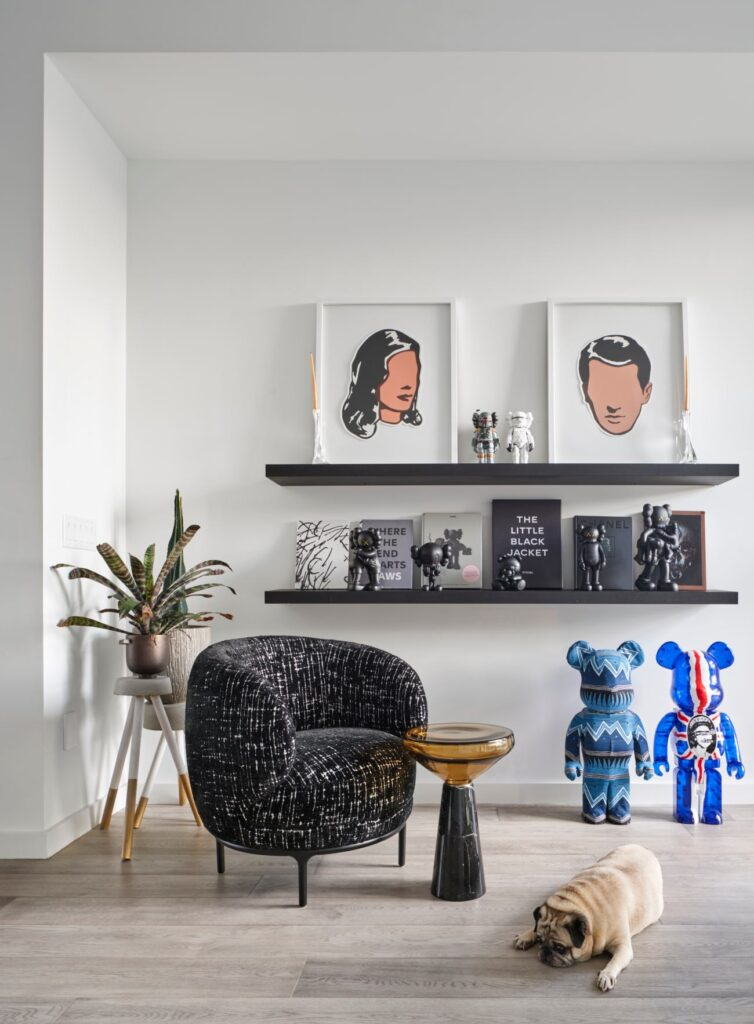 The lounge chair, from Avenue Road, is by Jamie Hayon. The side table, from Klaus, is by Stephen Veit. The prints, by Adriana Oliver, share shelf space with Kaws figurines. On the floor, Stussy 1000% and Sex Pistol 1000% Bearbrick figurines.