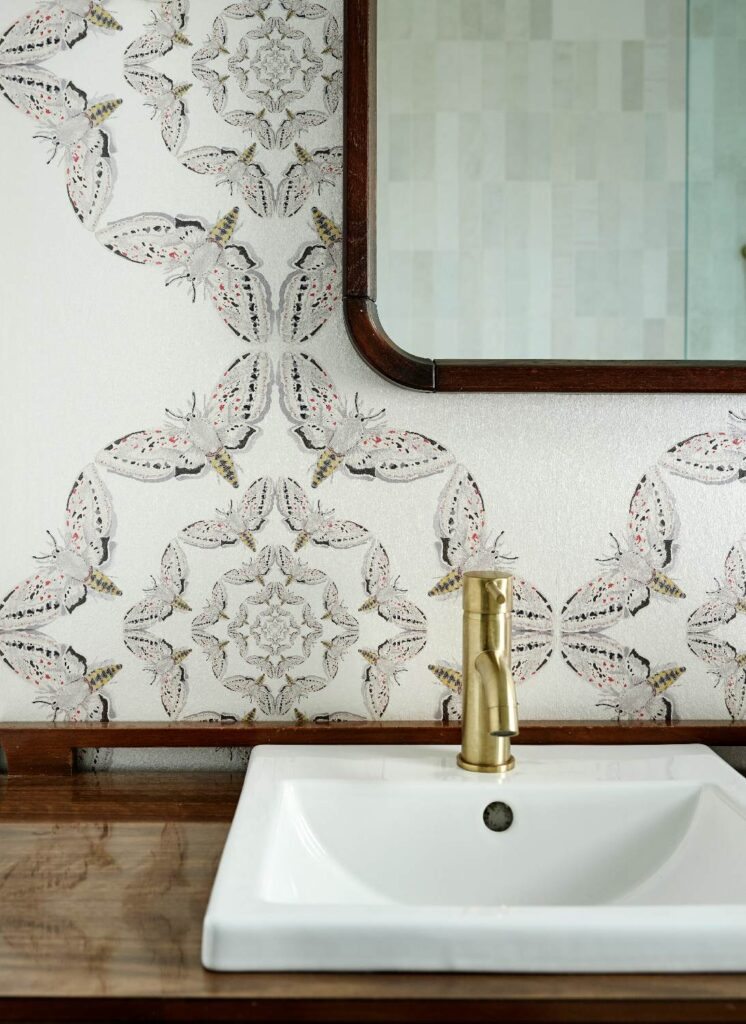The main washroom features Timorous Beasties' White Moth Circle wallpaper, from NewWall. The mirror and vanity are from Gone Vintage in Belleville.