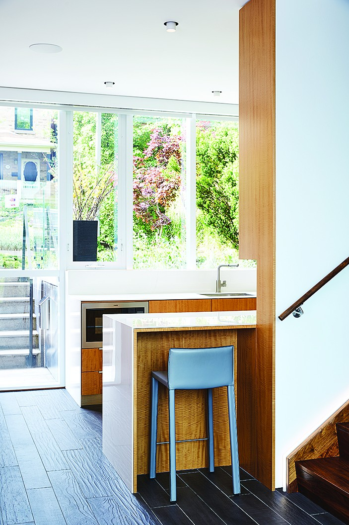 From the sidewalk, visitors step a metre below grade into the foyer beside the galley kitchen. Built by R&R Woodwork, it features bookmatched anigre wood topped with Laminam from Stone Tile.