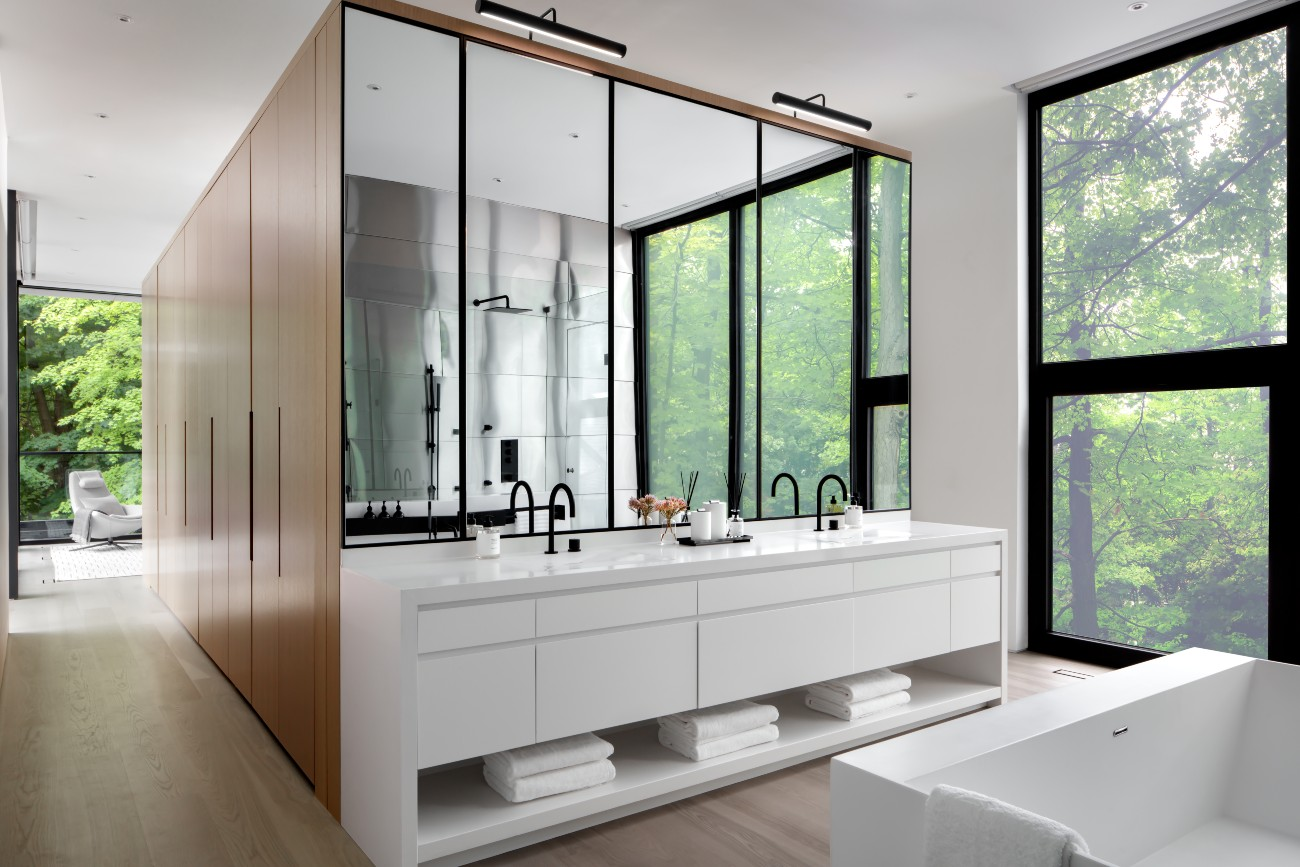 A wall unit housing walk-in closets and additional storage divides the main ensuite from the sleeping quarters. The shower wall, reflected in the quartz-topped vanity's mirrors, is clad in titanium – a direct reference to the front exterior wall. Soaker tub from Taps; faucets by Watermark.