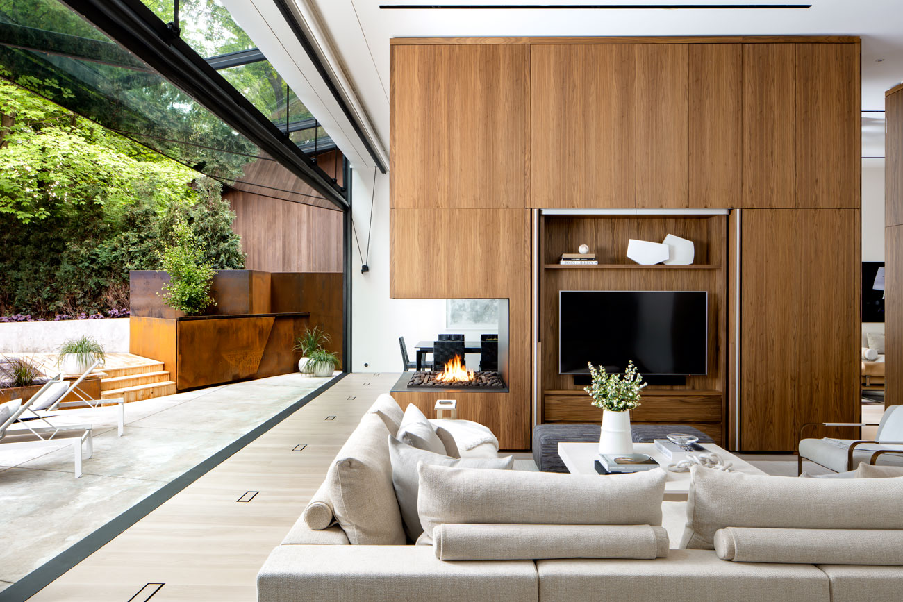 """At the back of the house are the home's two most mind-blowing features: the 12-metre-long hangar door, and the walnut """"Swiss Army knife"""" – a 15-metre-long unit (with millwork by Robert Design Group) that houses nine amenities. Sofa from Italinteriors; fireplace from Custom Fireplace Design"""