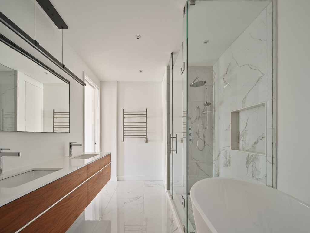 The ensuite shower features Statuario marble-look porcelain tile, by Mayfair, and Cabano fixtures. Vanity fixtures by Riobel.